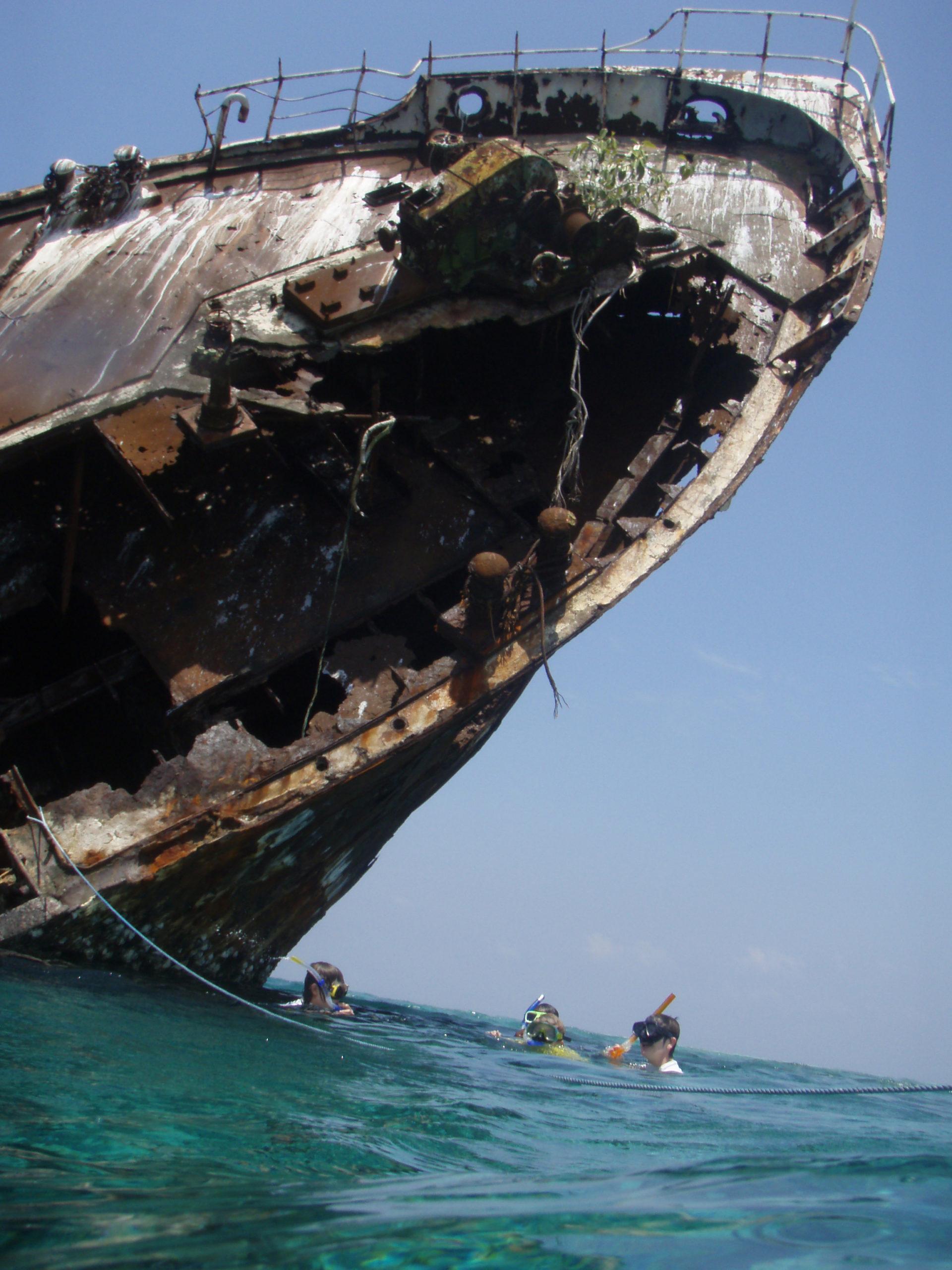 Après une navigation agitée entre deux atolls des Maldives, nous décidons de nous arrêter pour nous reposer dans un coin qui semble accueillant… en tout cas sur la carte en notre possession. La couleur de l'eau est magnifique, le soleil est haut dans le ciel et la passe facile à voir entre les nuances de bleus plus ou moins foncés. Mais ce qui m'interpelle, c'est l'immense monticule noir posé – tel un amer vraiment remarquable – à côté de la passe.  Que peut-il bien annoncer ?  Le courant est en notre faveur : on affale les voiles pour embouquer la passe au moteur. Il faut dire qu'elle n'est pas très large… Peut-être quatre fois la largeur de notre catamaran ! Les manœuvres s'enchaînent pour être bien aligné quand… je me rend compte que le monticule noir est en fait un cargo échoué sur la barrière de corail. Il ne s'est pas trompé de beaucoup, moins d'une centaine de mètres, mais cela a suffi pour qu'il finisse sa vie ici.  On ne résiste pas bien longtemps : on mouille à moins d'un demi mille de l'épave et on revient la découvrir en annexe pour l'une des plus belles plongées que nous ferons dans ces eaux… pourtant sublimes ! Pas de nom sur la coque, déjà complètement rouillée, ni aucun moyen d'identifier ce navire pour savoir depuis quand il est échoué ici. Il commence à se désagréger complètement et la partie sous l'eau est colonisée par des coraux multicolores. Tout autour du château arrière, c'est un balais de poissons aux couleurs étincelantes.   Mère nature a digéré le monstre de fer…   JC Guillaumin – SEAtizens